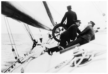 This photograph shows the crew lying on board the tilting deck of the Reliance, 1903 - A winch in the foreground.